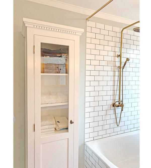 Weiße Vitrine mit Glastür im Bad aus Kiefer